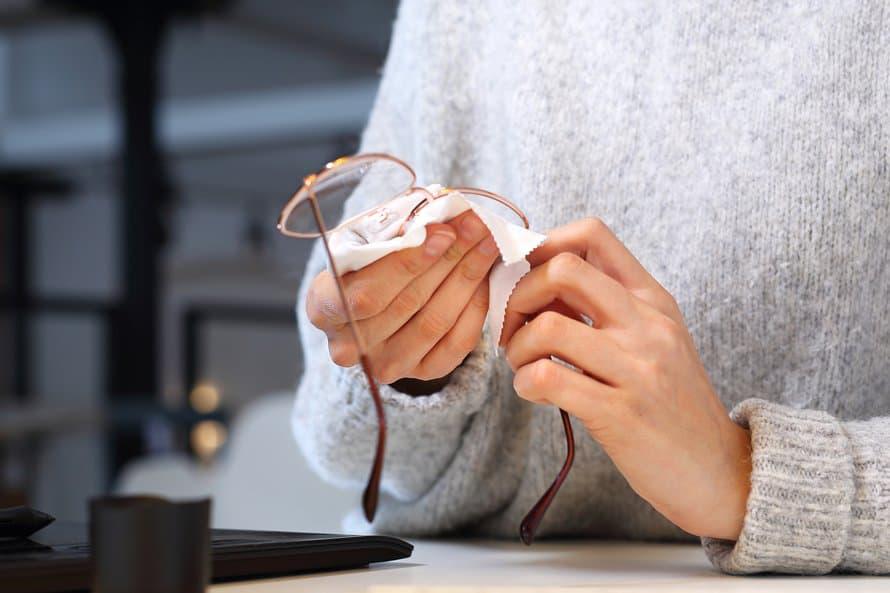 Imagem de mulher limpando óculos