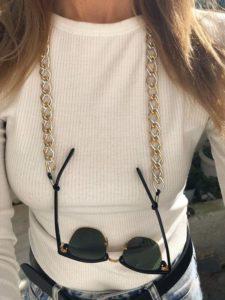 Imagem de mulher com óculos de sol com corrente de óculos grossa