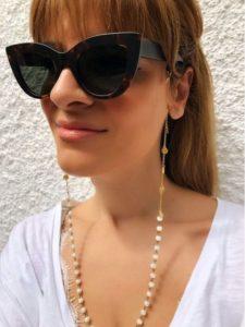 Imagem de mulher com óculos de sol com corrente de óculos pela frente