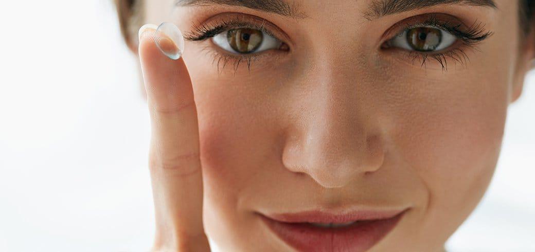 Imagem de mulher colocando lentes de contato descartáveis