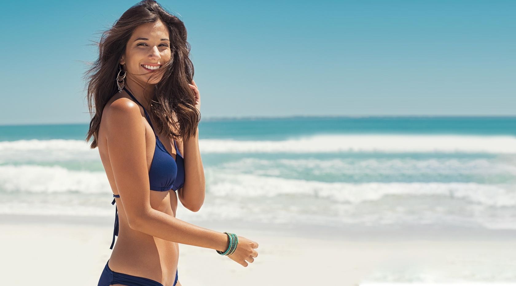 Imagem de mulher usando lentes de contato na praia