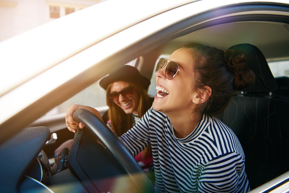Imagem de mulher dirigindo com óculos de sol